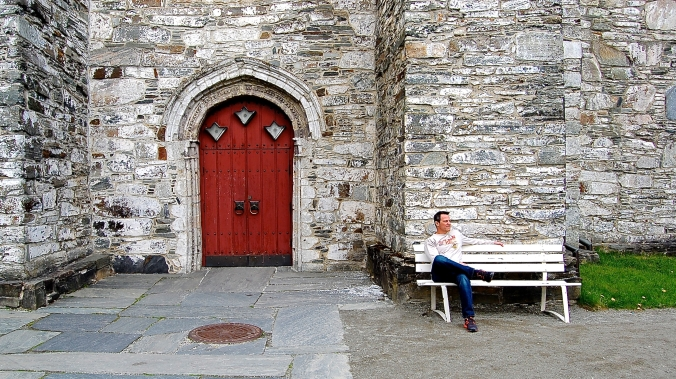 Lon sitting on a bench at The Kirk in Vossevangen, Norway